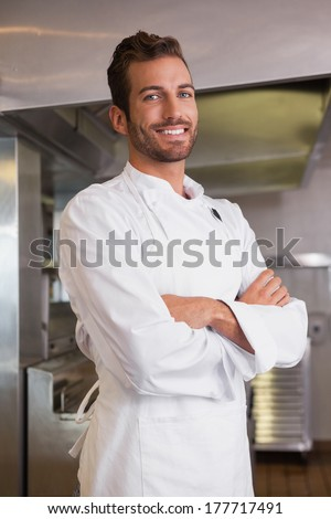 Happy chef standing with arms crossed in a commercial kitchen - stock photo