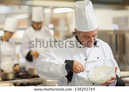 Happy chef whisking cream in kitchen - stock photo