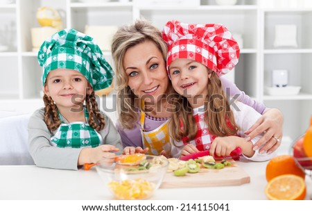 Happy chefs in the kitchen - woman and little girls portrait preparing fruit salad - stock photo