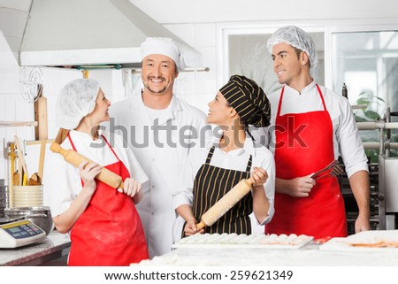Happy chefs looking at male colleague while preparing pasta in commercial kitchen - stock photo