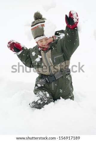 Happy chiild toddler, boy or girl, in snow licking  his cold hands  in winter.  - stock photo