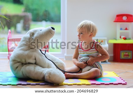 Happy child, adorable blonde toddler girl, playing doctor game with her teddy bear sitting comfortable on the floor in playroom at home, school or kindergarten - stock photo