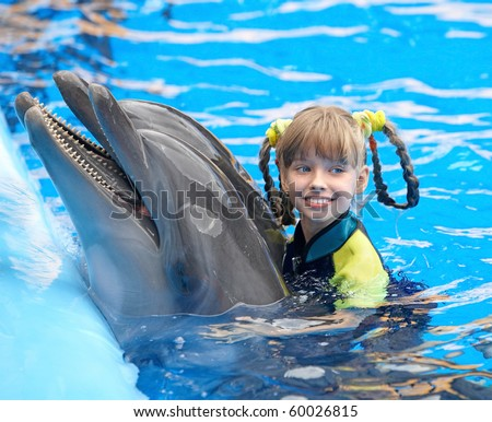 Happy child and dolphin in blue water. - stock photo