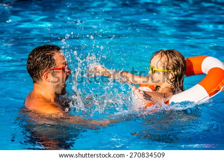 Happy child and father playing in swimming pool. Summer vacation concept - stock photo