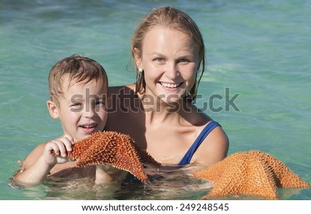 Happy child and mother bathing in sea and holding two starfish. Summer vacation in tropical countries - stock photo