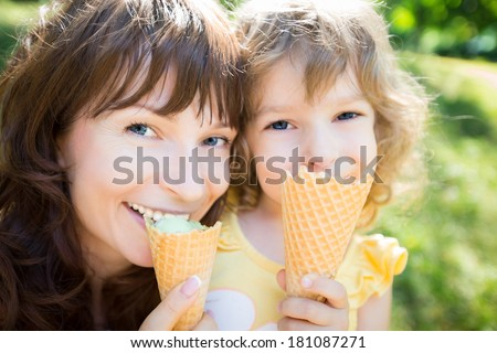 Happy child and mother eating ice-cream outdoors in summer park - stock photo