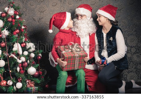 Happy child and Santa Claus with big gift or present box! Sitting at home near decorated Christmas tree. Boy and girl dressed in red Santa hat. Concept of traditional world celebration, family holiday - stock photo