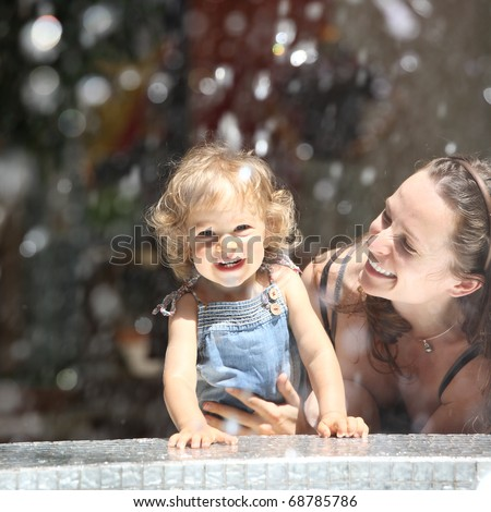 Happy child and woman in fountain splashes - stock photo