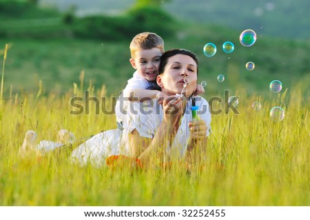 happy child and woman outdoor playing with soap bubble on meadow - stock photo
