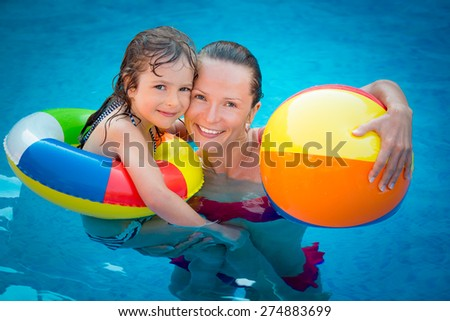 Happy child and woman playing in swimming pool. Summer vacation concept - stock photo