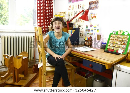 happy child at home sitting on her table in the childrens room - stock photo