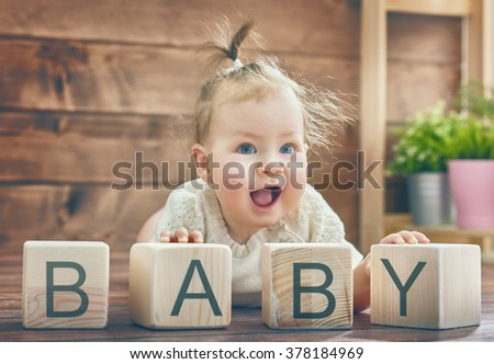 Happy child baby girl playing with blocks and having fun. Blocks have letters. The child puts the word Baby. - stock photo