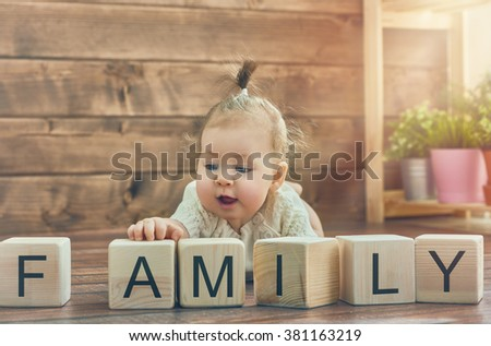 Happy child baby girl playing with blocks and having fun. Blocks have letters. The child puts the word Family. - stock photo