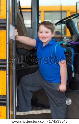 Happy child boarding school bus going back to school - stock photo