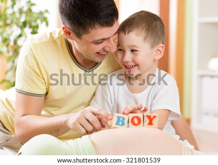 Happy child boy and his father playing with toys on belly of pregnant mother in home interior - stock photo