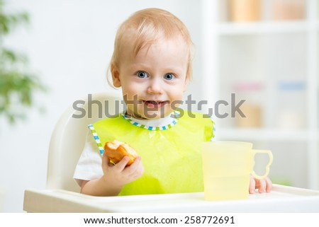 happy child boy eating food in highchair - stock photo