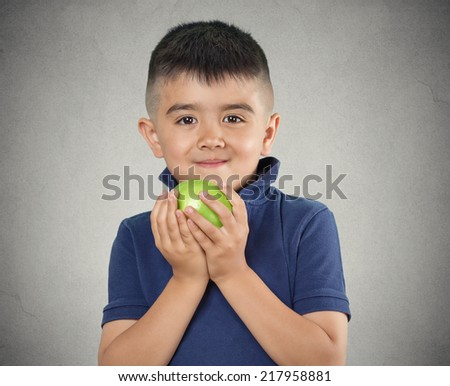 Happy child boy eating green apple smiling isolated grey wall background. Positive human emotions, face expressions. Healthy diet, food, nutrition concept - stock photo