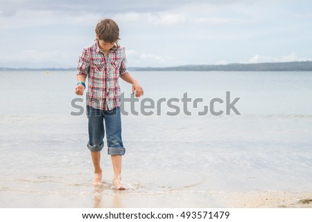 Happy child boy having fun on natural sea background