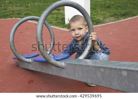 Happy child boy playing seesawing in green grass playground in park - stock photo