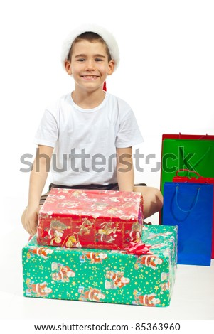 Happy child boy with Santa hat and blank t-shirt sitting on floor with legs crossed with Xmas gifts around him against white background - stock photo