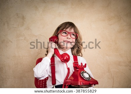 Happy child businessman with retro phone. Communication in business concept - stock photo