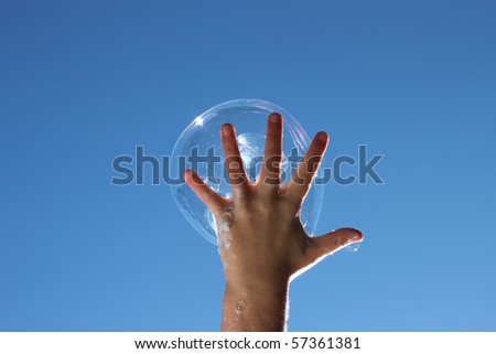 Happy child catches a bubble in one hand on a sunny day against a deep blue sky. - stock photo