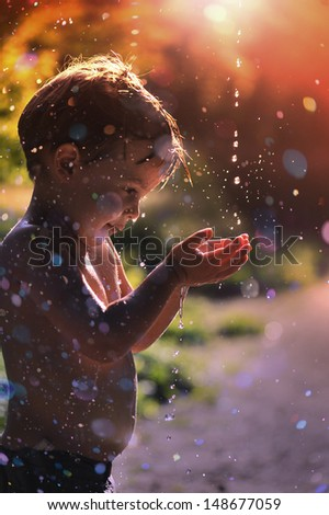 happy child catches a drop of water. - stock photo