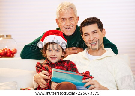 Happy child celebrating christmas with father and grandfather and gifts - stock photo