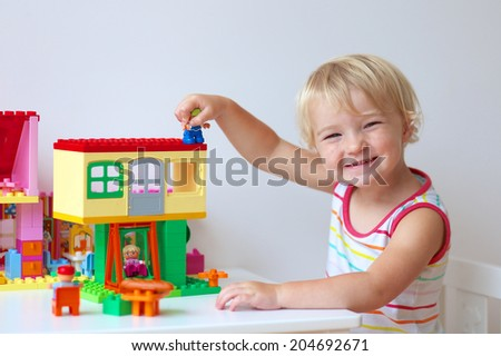 Happy child, cute blonde toddler girl having fun playing with colorful plastic blocks building house indoors at home, school or kindergarten - stock photo