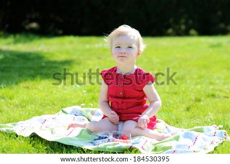Happy child, cute blonde toddler girl in beautiful red dress, enjoying healthy snack outdoors eating tasty sweet blueberries and redcurrants sitting on the blanket in the garden on a sunny summer day - stock photo