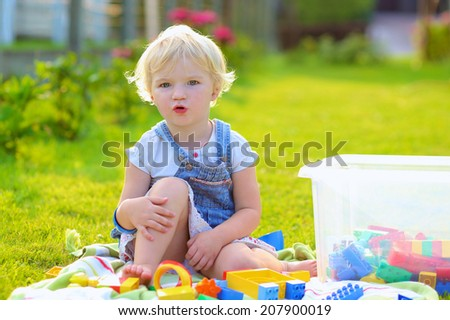 Happy child, cute blonde toddler girl playing with colorful plastic blocks sitting outdoors in the garden at the backyard of house or kindergarten