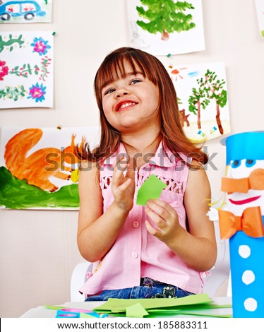 Happy  child cutting paper by scissors. - stock photo