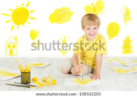 Happy child drawing with yellow color brush. Creativity concept. - stock photo