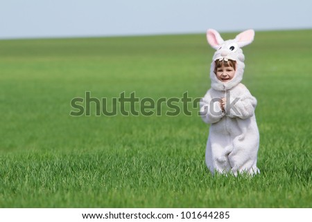 happy child dressed as rabbit on natural background (no-name costume) - stock photo