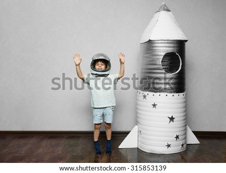 Happy child dressed in an astronaut costume playing with hand made rocket. - stock photo