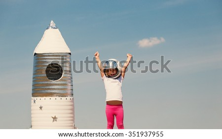 Happy child dressed in an astronaut costume playing with hand made rocket. Tinted photo. - stock photo