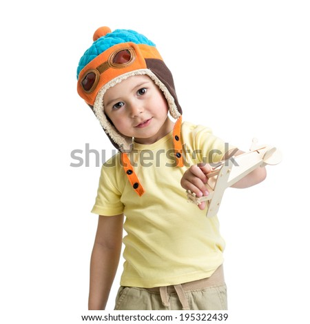 happy child dressed pilot and playing with wooden airplane toy - stock photo