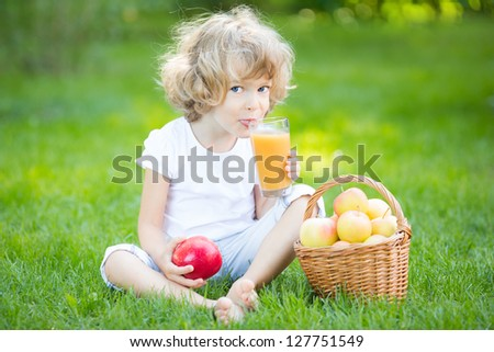 Happy child drinking apple juice in spring park - stock photo