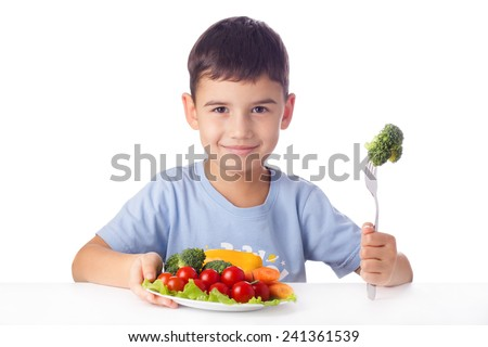 Happy child eating healthy vegetables - stock photo