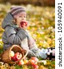 Happy child eating red apple in autumn park. Healthy lifestyles concept - stock photo