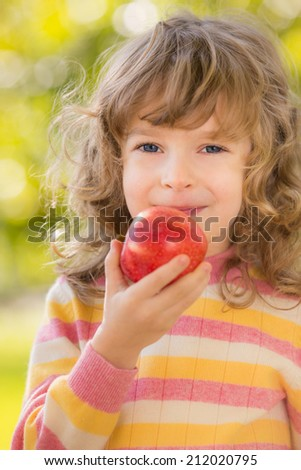 Happy child eating red apple outdoors in autumn park - stock photo