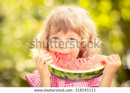 Happy child eating watermelon. Kid having picnic in autumn park