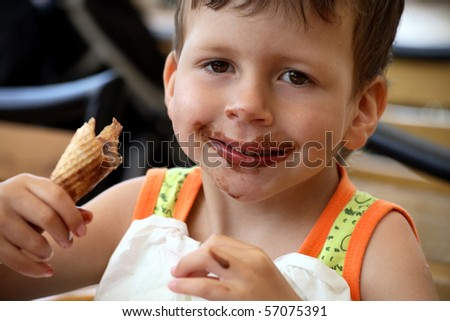 Happy child eats ice cream - stock photo