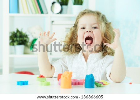 Happy child enjoying herself modeling with colorful clay - stock photo