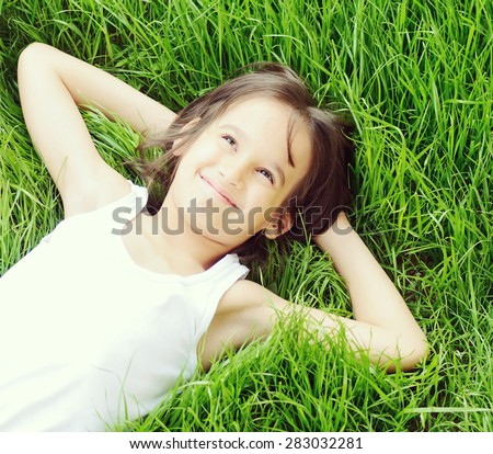 Happy child enjoying on grass field and dreaming - stock photo