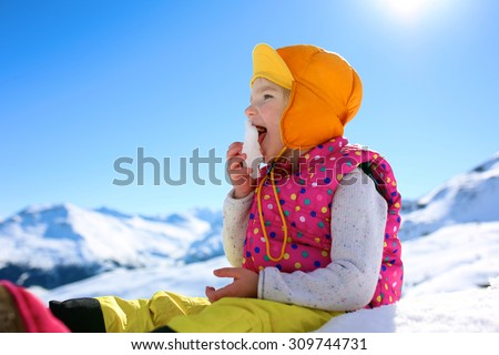 Happy child enjoying winter holidays in Alpine resort in Austria. Little girl playing in the snow. Active sportive toddler learning to ski. Kids having fun outdoors. Alps mountains in the background. - stock photo