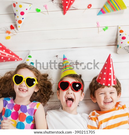 Happy child friend in carnival party, lying on a wooden floor. Happy childhood concept. High top view. - stock photo