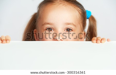 Happy child girl and a blank white poster billboard