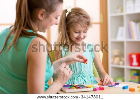 Happy child girl and mother sitting at table and playing with colorful clay toy - stock photo