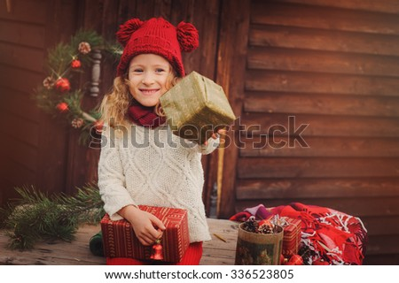 happy child girl celebrating christmas outdoor at cozy wooden country house, giving gift - stock photo